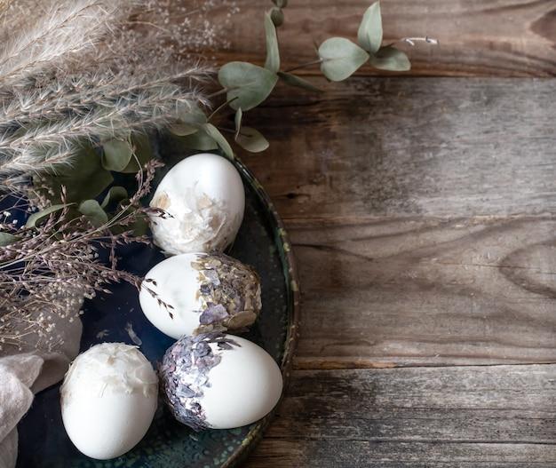 Wielkanocna kompozycja z ozdobnymi jajkami na drewnianej powierzchni kopii przestrzeni.