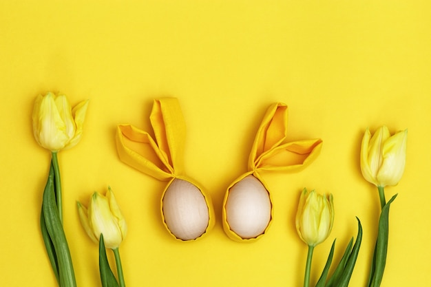 Wielkanocna kompozycja z ręcznie robioną kolorową pisanką z uszami z królika i bukietem świeżych żółtych kwiatów tulipana