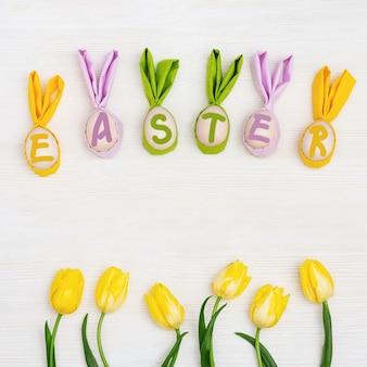 Wielkanocna kompozycja z ręcznie robionymi kolorowymi jajkami z uszami z królika i słowem wielkanocnym