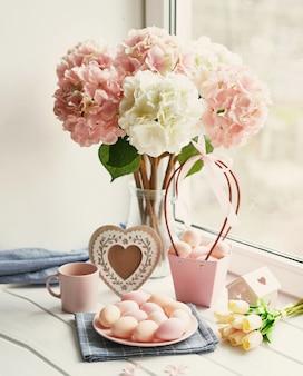 Wielkanocna kompozycja z różowymi i białymi hortensjami w wazonie, żółtymi tulipanami i różowymi jajkami