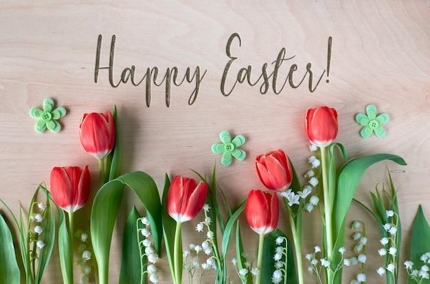 Wielkanocna kompozycja z wiosennymi kwiatami, tulipanami i konwalią na drewnie