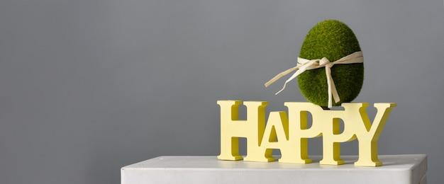 Wielkanocna kompozycja z zielonym jajkiem i drewnianym napisem szczęśliwy na szarym tle, miejsce na tekst