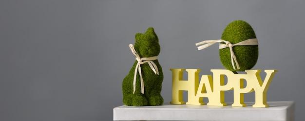 Wielkanocna kompozycja z zielonym jajkiem, króliczkiem i drewnianym napisem szczęśliwy na szarym tle, miejsce na tekst