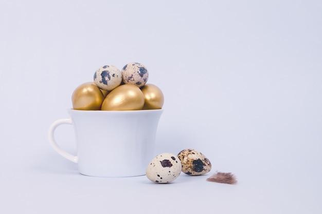 Wielkanocna kompozycja złotych ozdobnych i przepiórczych jaj w porcelanowym kubku na niebiesko