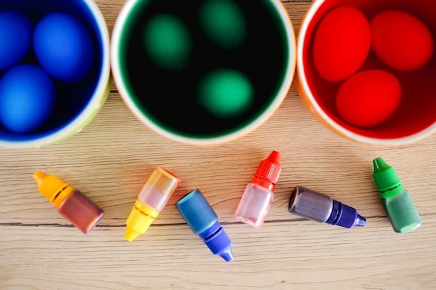 Wielkanocna koncepcja. barwienie pisanek. dekorowanie pisanek. kubki z płynną, jasną farbą i jajkami oraz jadalnymi kolorowymi farbami w butelkach na drewnianym stole