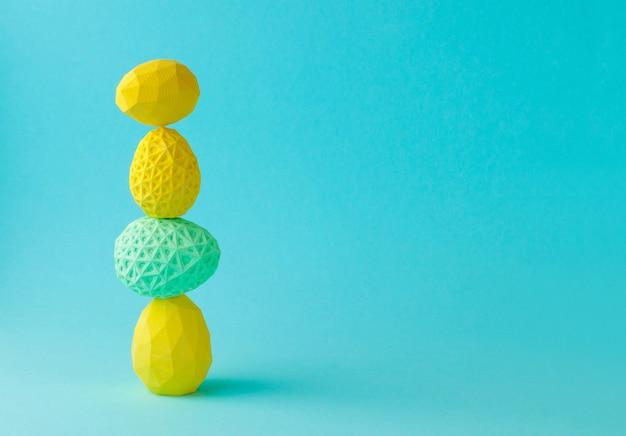 Wielkanocna koncepcja minimalistyczny wystrój. geometryczne pisanki stojące jeden na drugim na kolorowym tle z pustym miejscem na tekst.