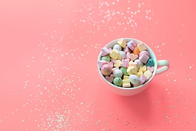 Wielkanocna koncepcja. słodcy cukierki i marshmallows w filiżance na różowym tle