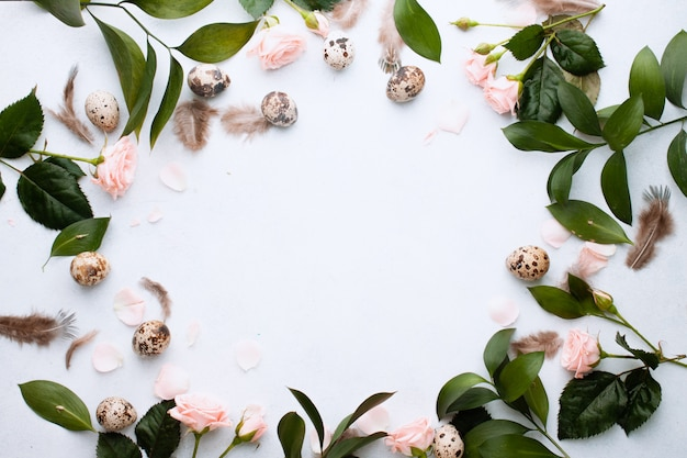 Wielkanocna koncepcja. wielkanoc koło ramki na baner z piór, gałęzi i pąków róży i jaj przepiórczych na białej ścianie z miejscem na tekst. widok z góry. leżał płasko. pocztówka na ferie wiosenne