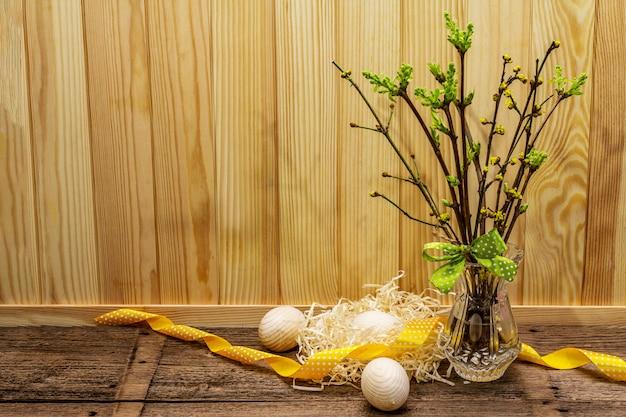 Wielkanocna koncepcja zero marnotrawstwa. wiosenne gałązki ze świeżymi zielonymi liśćmi. szklany wazon, drewniane jajka, gniazdo, wstążka w kropki.