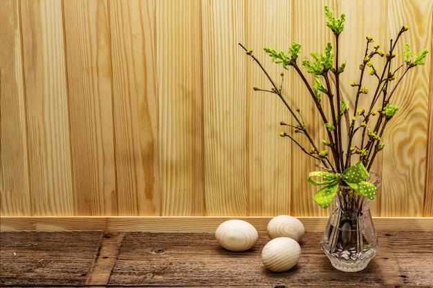 Wielkanocna koncepcja zero marnotrawstwa. wiosenne gałązki ze świeżymi zielonymi liśćmi. szklany wazon, drewniane jajka, wstążka w kropki.