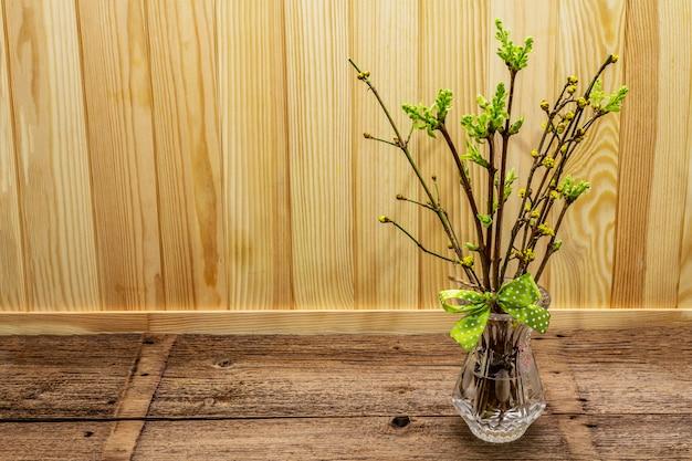 Wielkanocna koncepcja zero marnotrawstwa. wiosenne gałązki ze świeżymi zielonymi liśćmi. szklany wazon, kokardka w kropki.