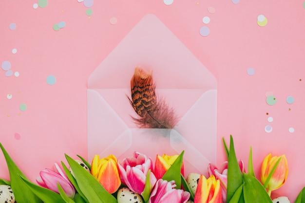 Wielkanocna koncepcja, złote dekoracje gwiazd, żywe konfetti i otwarta matowa przezroczysta koperta z piórami