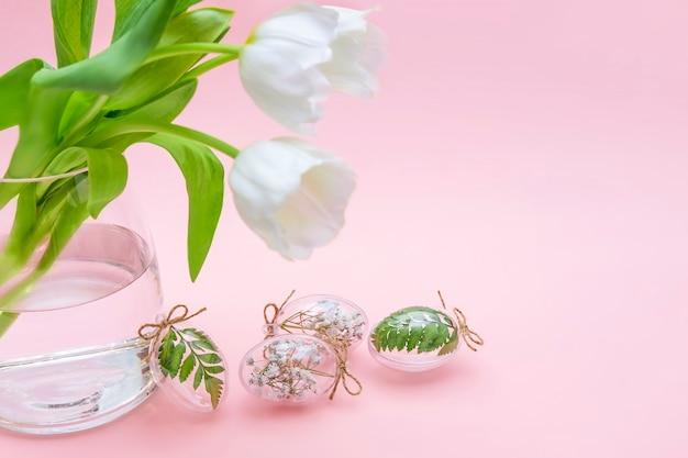 Wielkanocna minimalistyczna kompozycja, białe tulipany, przezroczyste szklane jajka wypełnione białymi kwiatami i liśćmi paproci na różowo