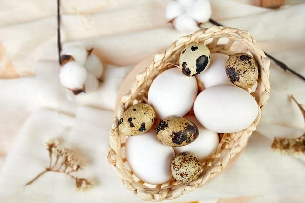 Wielkanocna płaska kompozycja z bawełnianymi kwiatami i pisankami w małym koszyku na tle tekstury tkaniny. wesołych świąt wielkanocnych, kopia przestrzeń.