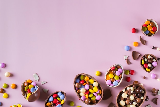 Wielkanocna ramka z czekoladowymi jajkami i słodyczami na różowym tle. skopiuj miejsce, widok z góry, płaski układ