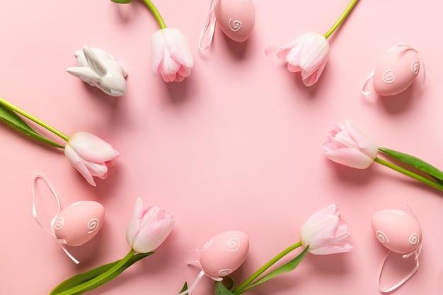 Wielkanocna ramka z jajkami, króliczkiem, różowymi tulipanami na różowym tle.