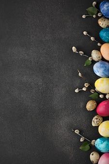 Wielkanocna ramka z kolorowych jaj i gałęzi z zielonymi liśćmi.