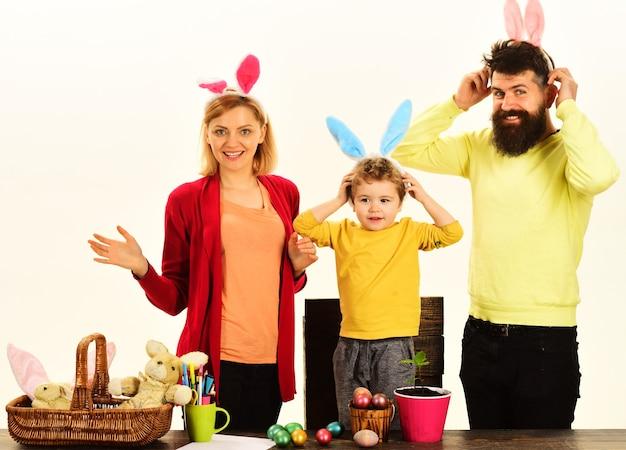 Wielkanocna rodzina z kolorowymi pisankami na na białym tle, miejsca na tekst.