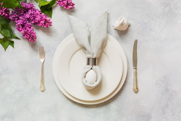 Wielkanocna romantyczna kolacja. eleganckie nakrycie stołu z kwiatami bzu na lekkim stole.