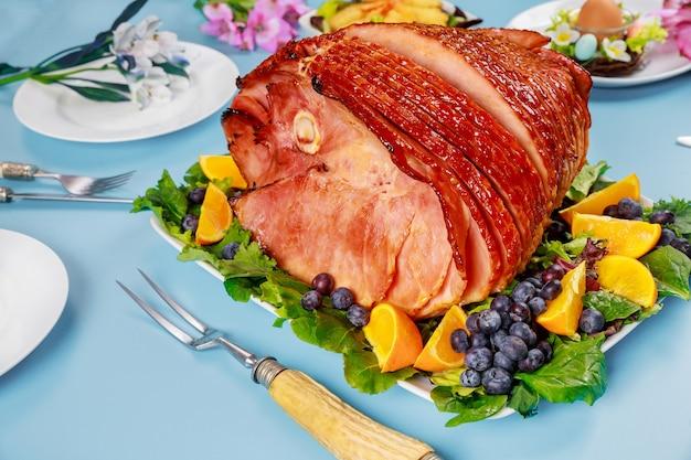 Wielkanocna spiralna szynka glazurowana na świątecznym stole. obiad wielkanocny.