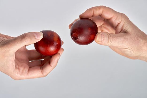 Wielkanocna tradycja rozbijania jajek, dwie ręce trzymają jajka i próbują rozbić sobie nawzajem jajko