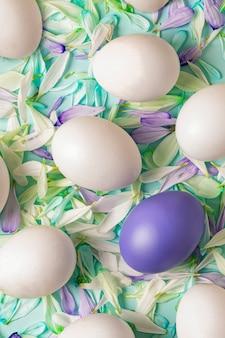 Wielkanocna wiosna tło. białe jajka na zieleni z kropkami płatków kwiatu chryzantemy - białe, zielone i niebieskie.