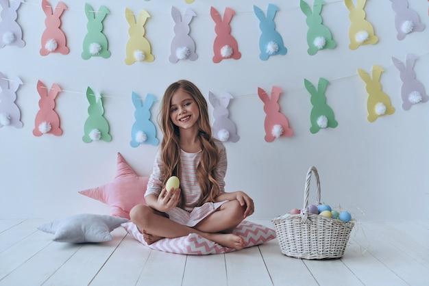 Wielkanocna zabawa. śliczna mała dziewczynka trzymająca pisanka i uśmiechnięta