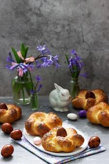 Wielkanocne bułeczki, kolorowe jajka i kwiaty na szarym tle betonu.