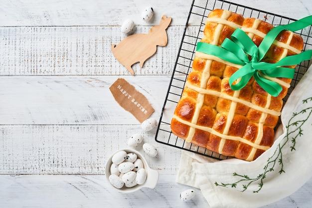 Wielkanocne bułeczki z gorącym krzyżem. tradycyjne śniadanie i wielkanocne pieczenie świąteczne dekoracje rabbiton białe drewniane tła. jasne kolory, widok z góry na drewnianym stole.