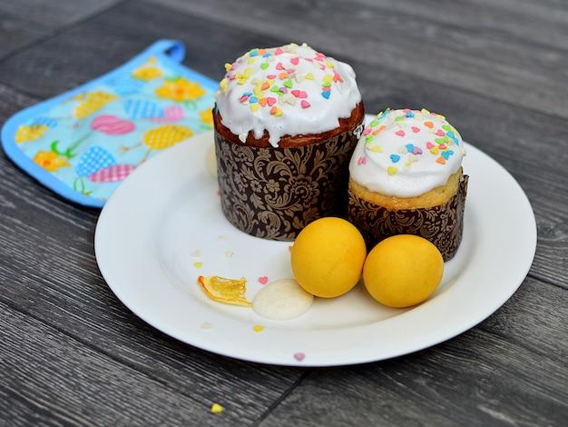 Wielkanocne ciasta na białej płytce, ozdobione białym lukrem, z wielobarwnymi sercami i dwoma żółtymi pisankami