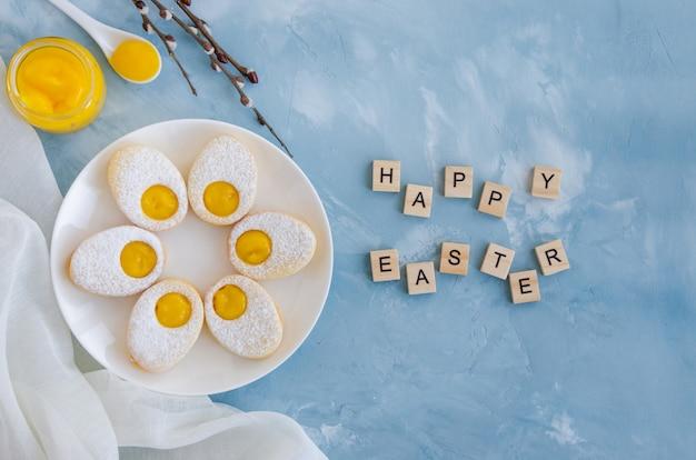 Wielkanocne ciasteczka w formie pisanki z cukrem pudrem i kremem cytrynowym na białym talerzu na jasnoniebieskim tle betonu. kartka z życzeniami. wielkanocny tło