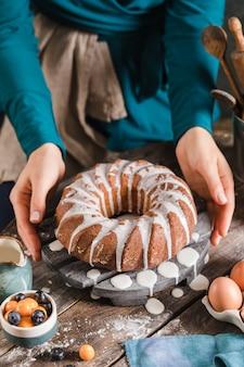 Wielkanocne ciasto drożdżowe na drewnianym talerzu trzymane przez kobiece ręce, gdy jest podawane do stołu