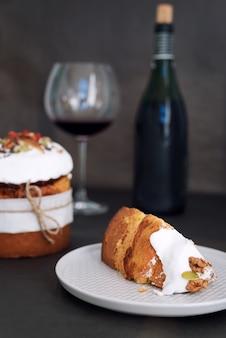 Wielkanocne ciasto i kieliszek czerwonego wina. wielkanocny skład z ortodoksyjnym słodkim chlebem, kulich i butelką wina na ciemnym tle