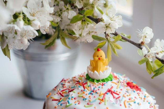 Wielkanocne ciasto ozdobione lukrem pisklęciem i perłą cukrową posypane kwitnącymi gałęziami drzew na tle