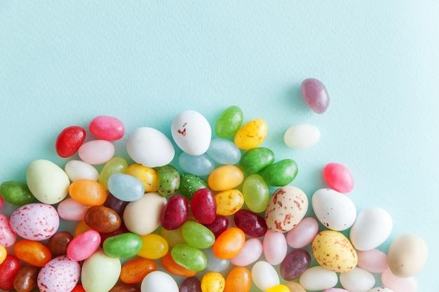 Wielkanocne cukierki czekoladowe jajka i galaretki na białym tle na modnym pastelowym niebieskim tle