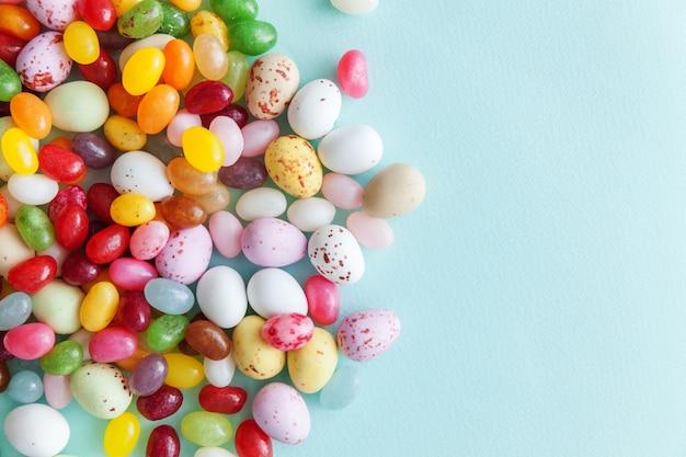 Wielkanocne cukierki czekoladowe jajka i galaretki słodycze na białym tle na niebieskim stole