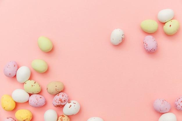 Wielkanocne cukierki czekoladowe jajka i galaretki słodycze na białym tle na różowym stole