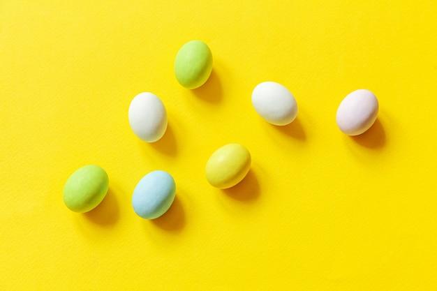 Wielkanocne cukierki czekoladowe jajka kolorowe pastelowe słodycze i zabawka króliczek na białym tle na modnym żółtym tle
