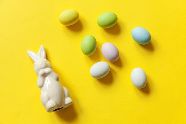 Wielkanocne cukierki czekoladowe jajka słodycze i zabawka królik na białym tle na modny żółty