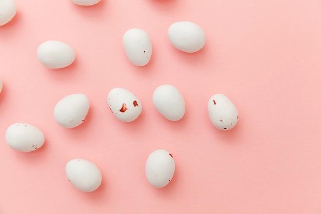 Wielkanocne cukierki czekoladowe jajka słodycze na białym tle na różowy stół