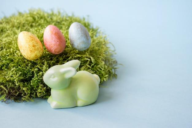 Wielkanocne figurki i barwioni jajka na błękitnym tle