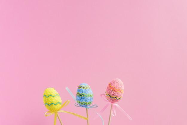 Wielkanocne fioletowe, żółte i niebieskie zdobione jaja stoją na drewnianych patyczkach na różowym tle. minimalna koncepcja wielkanocy. szczęśliwa kartka wielkanocna