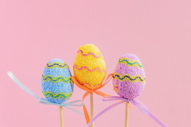 Wielkanocne fioletowe, żółte i niebieskie zdobione jajka stoją na drewnianych patyczkach. minimalna koncepcja wielkanocy. szczęśliwa kartka wielkanocna