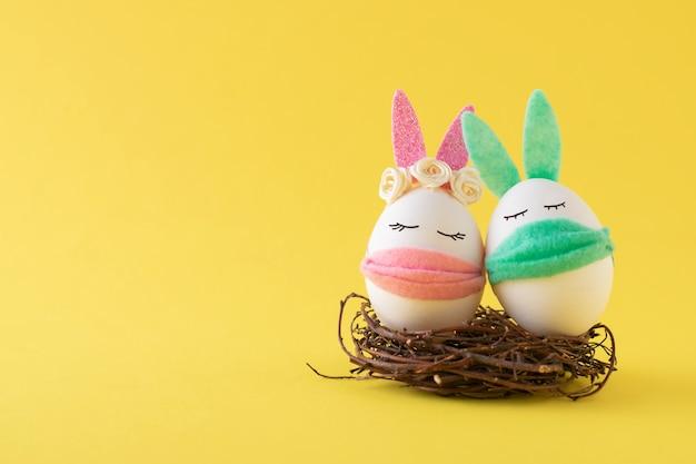 Wielkanocne jaja króliki w maskach medycznych z miejsca na kopię. koncepcja covid-19