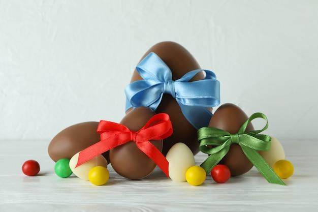 Wielkanocne jajka czekoladowe i cukierki na białym drewnianym stole