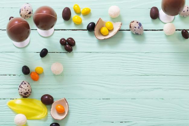 Wielkanocne jajka czekoladowe i cukierki na zielonej powierzchni drewnianych