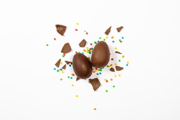 Wielkanocne jajka czekoladowe i kolorowe dekoracje na lekkiej powierzchni. wielkanocny pojęcie, wielkanocne smakołyki. . leżał płasko, widok z góry