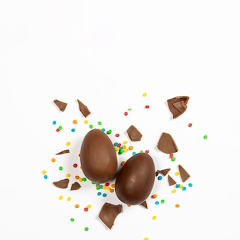 Wielkanocne jajka czekoladowe i kolorowe dekoracje na lekkiej powierzchni. wielkanocny pojęcie, wielkanocne smakołyki. plac. leżał płasko, widok z góry