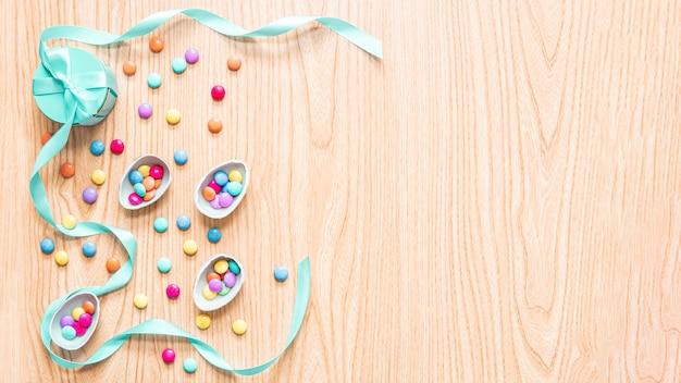 Wielkanocne jajka czekoladowe na tle drewna z kolorowe cukierki bonbon, wstążki, pudełka. świąteczna koncepcja, miejsce