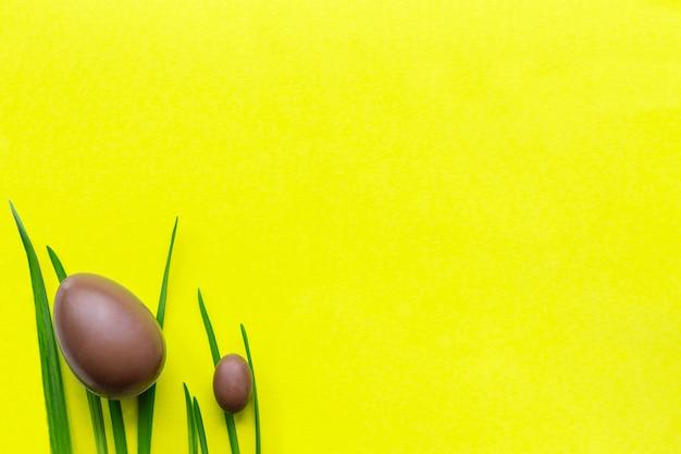 Wielkanocne jajka czekoladowe na trawie, duże i małe. żółte tło, zielone długie źdźbła trawy w lewym dolnym rogu. miejsce na twój tekst.